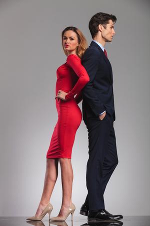 Foto de young elegant couple standing back to back in studio, woman in red dress, man in suit - Imagen libre de derechos
