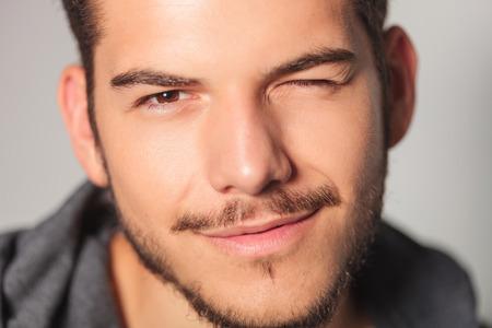Photo pour smilling young man is winking his eye , closeup picture in studio - image libre de droit