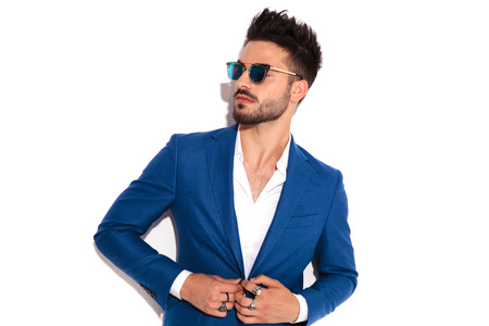 Photo for elegant man wearing sunglasses buttoning his suit and looks away to side on white background - Royalty Free Image