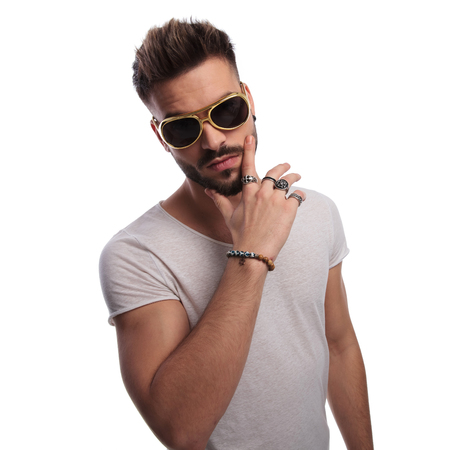 Photo for too cool for school young casual man holding hand on chin and wearing sunglasses on white background - Royalty Free Image