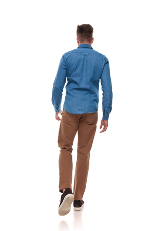 Foto de back view of young man in casual clothes walking on white background, full length picture - Imagen libre de derechos
