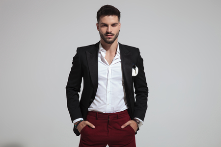 Photo pour portrait of relaxed fashion man wearing black suit and red pants holding pockets while standing on light grey background - image libre de droit