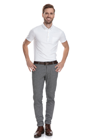 Foto de happy young smart casual man with hands on waist standing on white background - Imagen libre de derechos