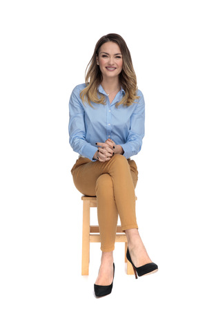 Foto de young casual dressed woman sitting on wooden chair with legs crossed and waiting for interview, full body picture - Imagen libre de derechos