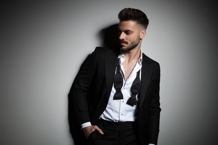 Foto de handsome man in tuxedo with undone collar holding hand in pocket on dramatic background - Imagen libre de derechos
