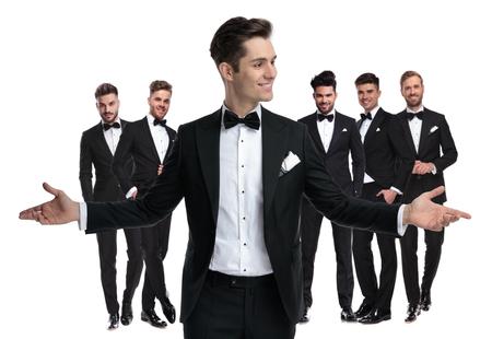 Foto de happy young groom welcomes you to be his best man , standing in front of his elegant team of men on white background - Imagen libre de derechos