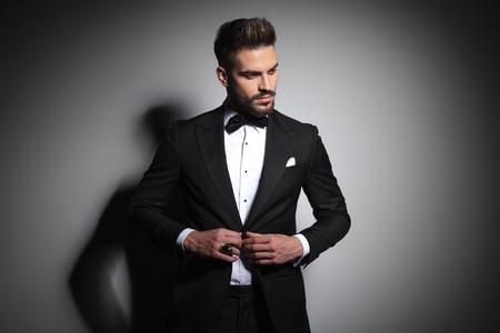 Photo pour fashion guy in black tuxedo unbuttoning his suit on gray studio background - image libre de droit