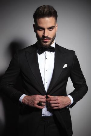 Photo pour model guy in black tuxedo unbuttoning his suit on dramatic studio background - image libre de droit