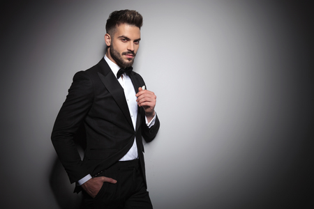 Photo pour handsome young guy in black tuxedo holding hand in pocket on dramatic studio background - image libre de droit