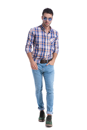 Confident guy walking forward and holding on of his hand in his pocket while wearing a pair of sunglasses and a checkered shirt on white studio background