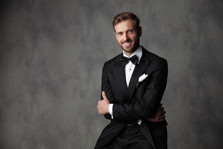 Jolly groom sitting with his arms crossed and looking at the camera while wearing a black tuxedo on gray studio background