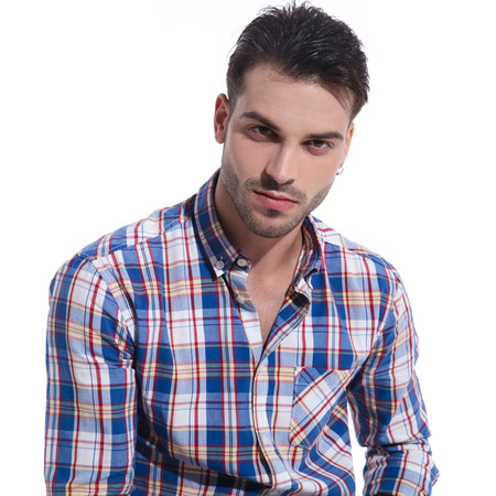 Close up of a handsome guy romantically looking at the camera while wearing a checkered unbuttoned shirt on white studio background