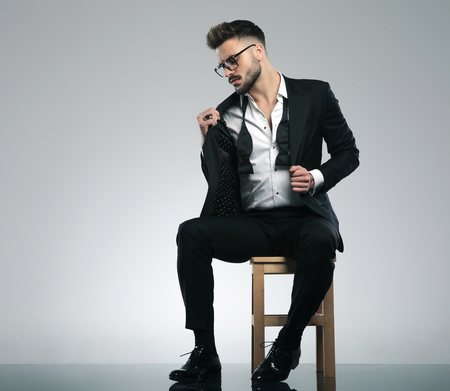 Photo for Sexy guy adjusting his jacket and looking to the side while wearing glasses and a black tuxedo, sitting on gray studio background - Royalty Free Image
