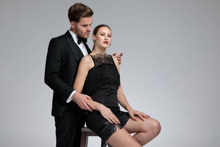 Photo for Handsome young man dressed in a tuxedo standing and embracing his girlfriend from behind while she is sitting on chair with her arms on her legs on gray studio background - Royalty Free Image