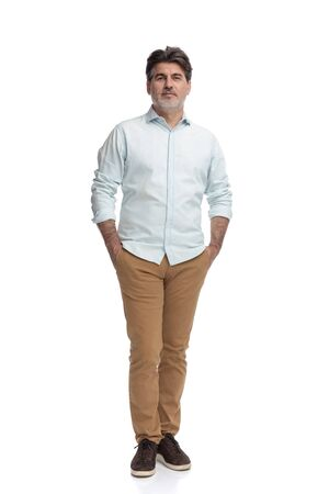 Foto de Casual old man standing with both hands in his pockets while wearing a white shirt and brown pants on white studio background - Imagen libre de derechos