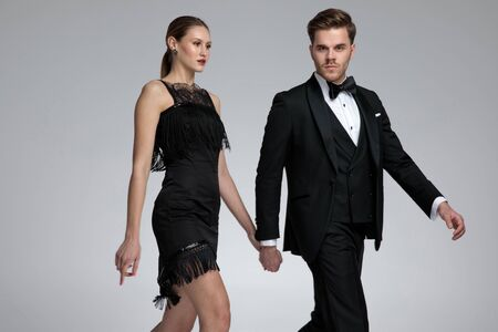 Photo pour Serious looking couple holding hands and stepping to the side while he is confidently looking to the camera and wearing a tuxedo on gray studio background - image libre de droit