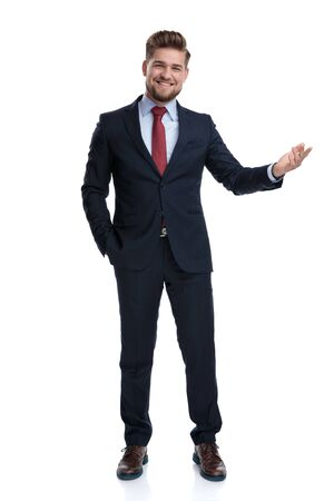 Photo pour Cheerful businessman presenting with his hand in his pocket while laughing and wearing a blue suit, standing on white studio background - image libre de droit