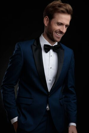 Foto de Positive young man laughing while holding his hand in his pocket and looking down, wearing a blue tuxedo while standing on black studio background - Imagen libre de derechos