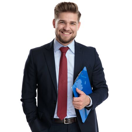 Photo for Jolly businessman laughing and holding a clipboard while holding his hand in his pocket and wearing a blue suit, standing on white studio background - Royalty Free Image