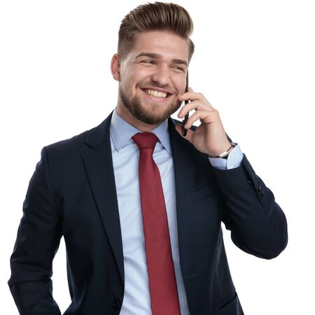 Photo for Jolly businessman laughing and talking on his phone while looking to the side and wearing a blue suit, standing on white studio background - Royalty Free Image