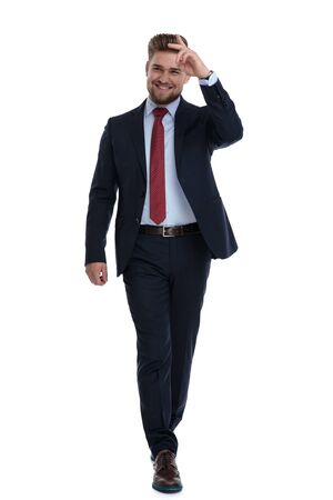 Foto per Elegant businessman stepping and gesturing a military salute while wearing a blue suit and laughing on white studio background - Immagine Royalty Free