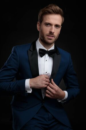 Photo for Confident young man about to take out a surprise from his blue tuxedo while sitting on black studio background - Royalty Free Image