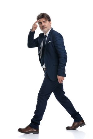 Foto per Side view of a businessman gesturing a military salute and walking while wearing a blue suit and tie on white studio background - Immagine Royalty Free