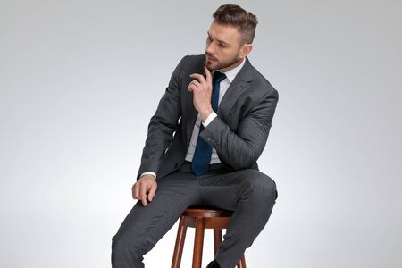 Photo pour pensive young businessman sitting on stool and wonders about something on grey background - image libre de droit