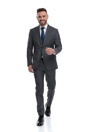 Photo pour confident young businessman wearing suit and tie is walking forward , isolated on white background - image libre de droit