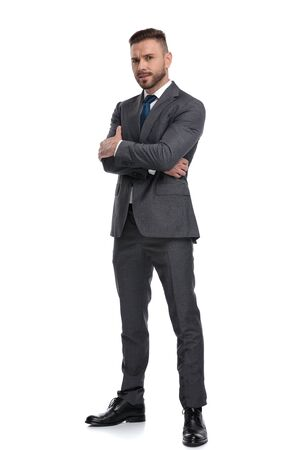 Photo pour confident young business man standing with hands crossed, isolated on white background - image libre de droit