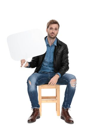 Photo for young casual man with black leather jacket is sitting on a wooden chair holding a speech bubble on one hand happy on white studio background - Royalty Free Image