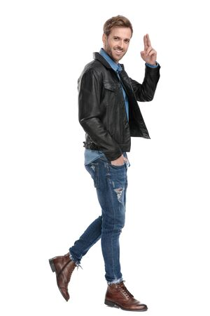 Photo for side view of a young casual man with black leather jacket walking with one hand in pocket while saluting happy on white studio background - Royalty Free Image