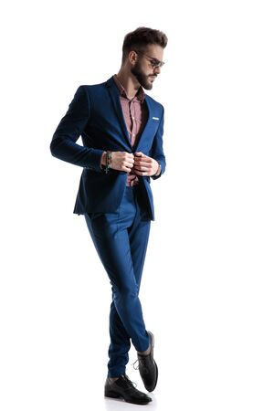 Photo pour gorgeous formal business man in blue suit with beard and sunglasses is standing with legs crossed and fixing his jacket while looking down pensive on white studio background - image libre de droit