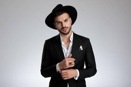 Foto de arrogant young model wearing tuxedo and black hat, arranging shirt and looking to side, on grey background in studio - Imagen libre de derechos