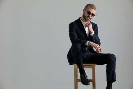 Photo pour handsome formal business man wearing a navy suit and sunglasses sitting with one leg resting on a chair and touching his chin while looking at camera pensive on gray studio background - image libre de droit