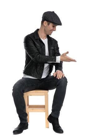 Photo pour good looking casual man wearing a black leather jacket and hat sitting and presenting to a side happy while looking down against white studio background - image libre de droit