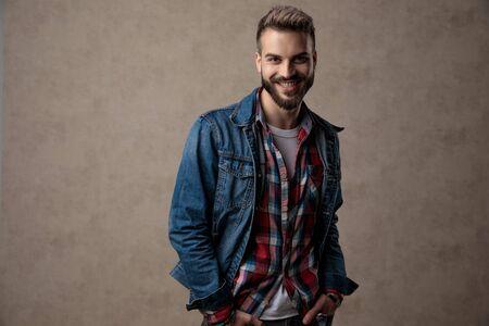Foto de happy casual man wearing blue denim jacket, smiling and holding hands in pockets, on brown background in studio - Imagen libre de derechos