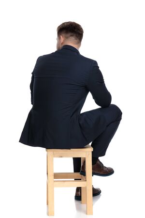 Photo pour back view of young businessman looking to side and thinking, sitting isolated on white background in studio - image libre de droit