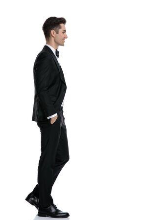 Foto de side view of smiling young groom in tuxedo walking isolated on white background in studio, full body - Imagen libre de derechos