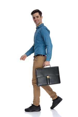 Photo pour side view of young man smiling and holding suitcase, walking isolated on white background, full body - image libre de droit