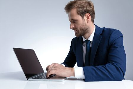 Photo pour Side view of a handsome businessman working and writing on his laptop while wearing a blue suit and sitting on gray studio background - image libre de droit