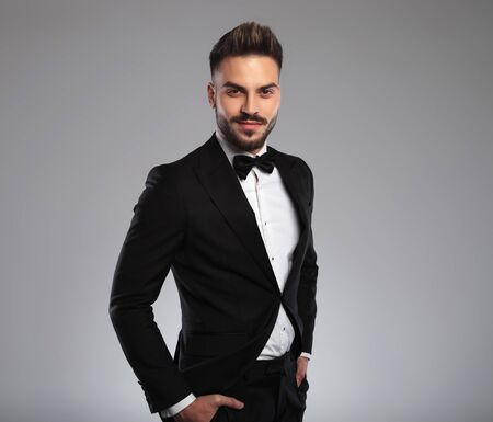 Photo pour Confident model holding his hands in his pockets and smiling while wearing tuxedo, walking on gray studio background - image libre de droit