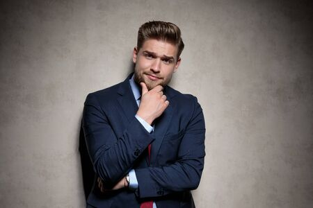 Foto de young formal guy wearing navy suit standing and touching chin thoughtful on gray studio background - Imagen libre de derechos