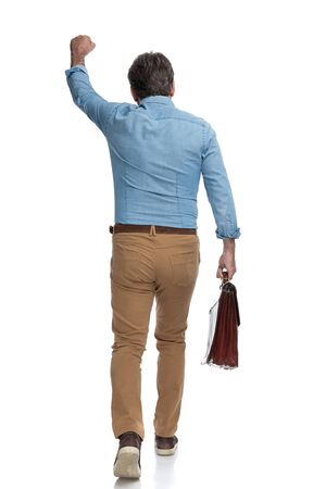 Photo pour Rear view of a positive casual man celebrating and holding his briefcase while stepping on white studio background - image libre de droit