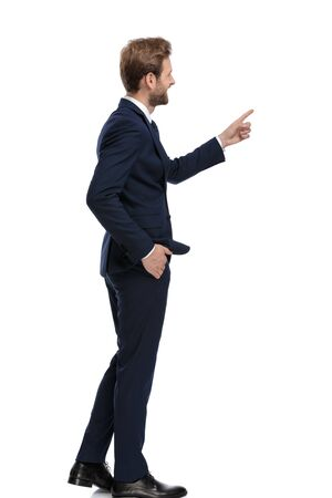 Photo for happy businessman in navy blue suit pointing finger and walking isolated on white background, full body - Royalty Free Image