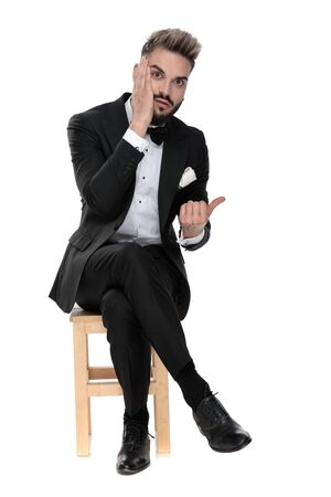 Photo pour gorgeous businessman wearing black tuxedo sitting on a wooden chair with legs crossed and touching his face while pointing aside worried on white studio background - image libre de droit