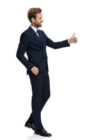 Photo for side view of happy businessman smiling and making thumbs up sign, walking isolated on white background, full body - Royalty Free Image