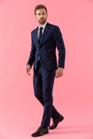 Photo pour Pensive businessman curiously looking away while walking on pink studio background - image libre de droit