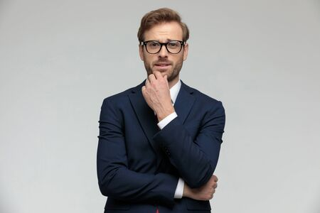 Photo pour young businessman wearing suit and eyeglasses standing and pondering a decision pensive on gray studio background - image libre de droit