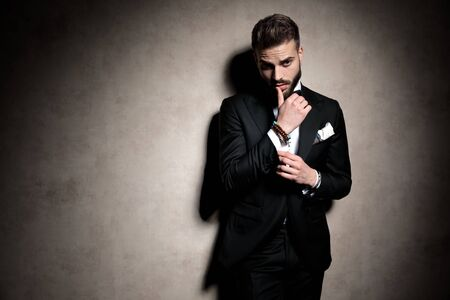 Foto de sexy elegant man in tuxedo looking to side and touching lips in a fashion pose on brown background in studio - Imagen libre de derechos